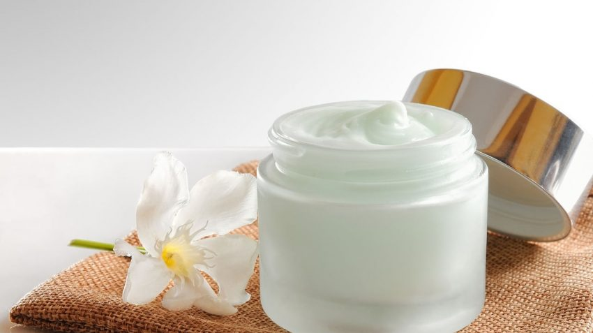 Open box of facial cream with the flower