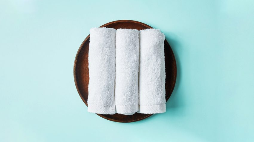 Three white towels on cyan background ready for facial tap