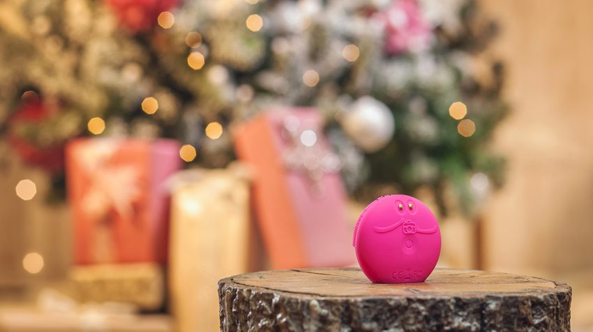 FOREO LUNA fofo standing on a log with Christmas tree and presents