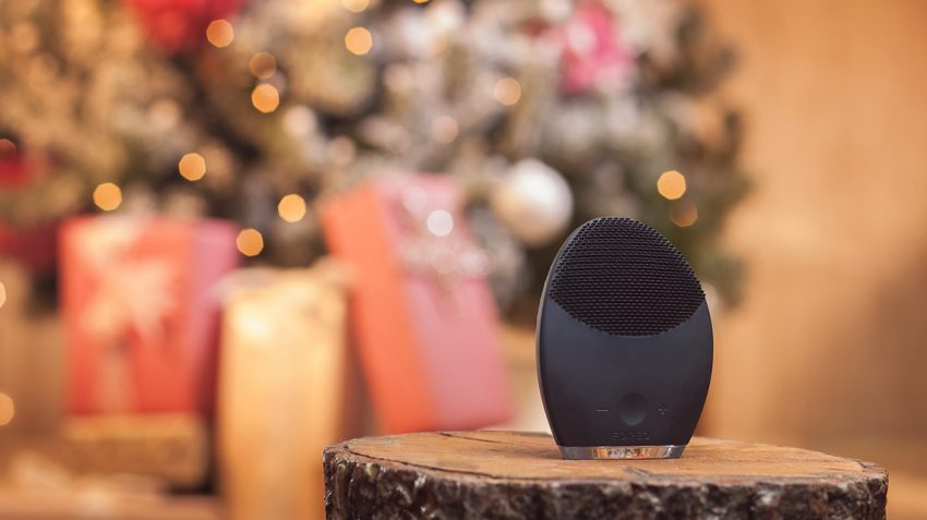 FOREO LUNA for MEN standing on a log with Christmas tree and presents