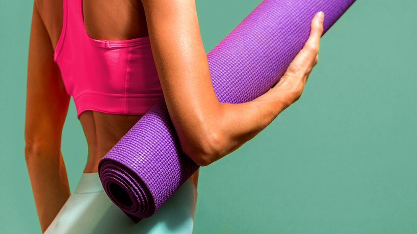 Girl holding purple yoga mat and getting ready to work out