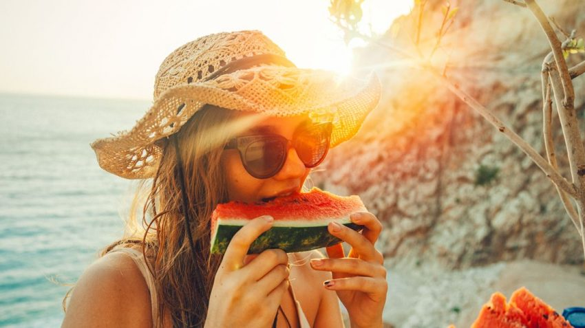 Girl eating watermelon during sunrise