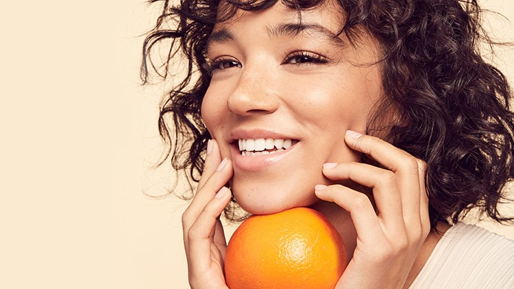 Girl with short curly hair smiling and holding orange