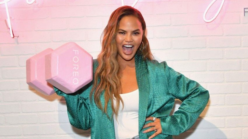 Chrissy Teigen cheekily smiling and lifting a FOREO weight