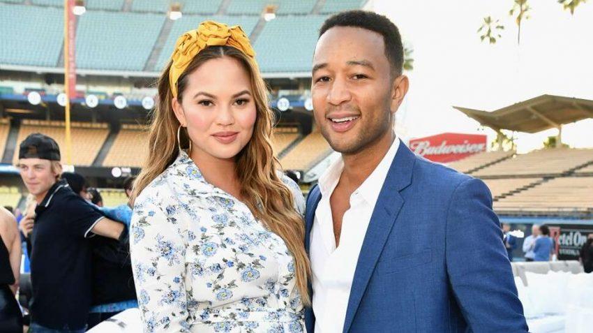 Chrissy Teigen standing next to husband John Legend