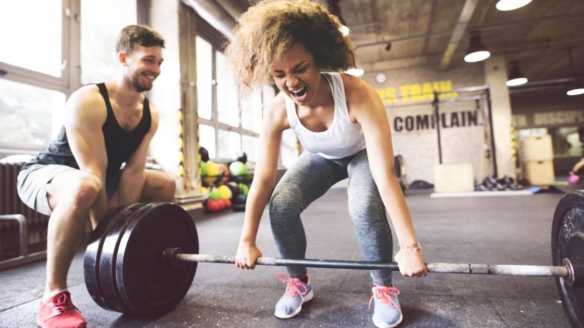 Girl trying hard to lift weight while trainer helps