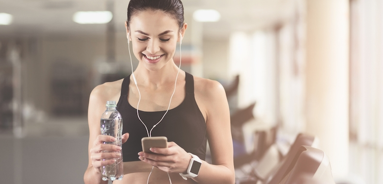 Girl in gym holding water bottle and listening to music smiling