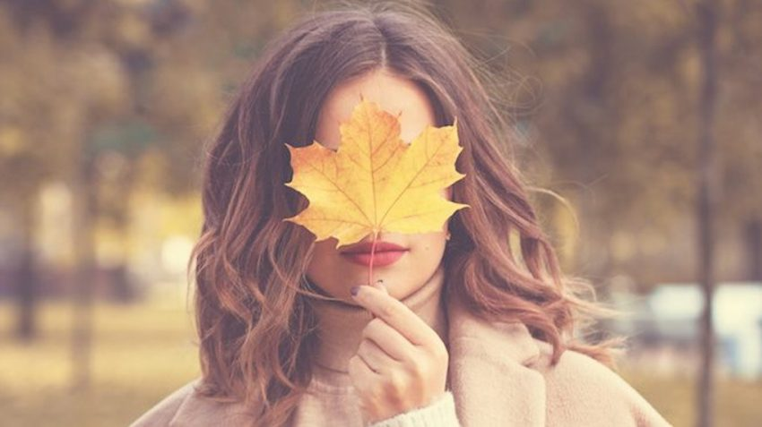 Women with the yellow leaf in front of her face