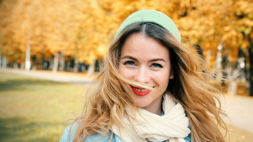 girl in front of autumnal background with hair infront of face