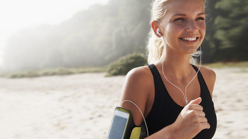 girl running on beach listening to music
