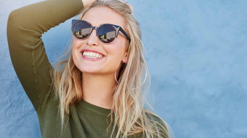 Confident girl wearing sunglasses and smiling
