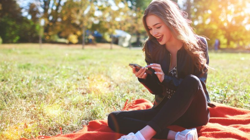 Girl smiling at her phone outside on picnic blanket