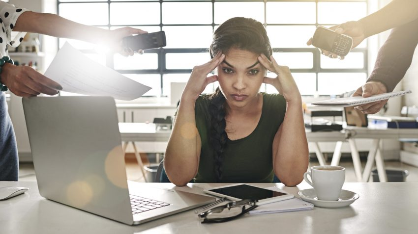 Woman in office environment visibly stressed