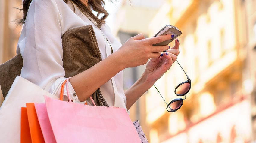 Woman carrying shopping bags while looking at phone
