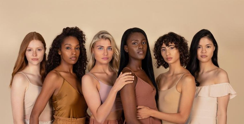 Models standing together with different skin tones