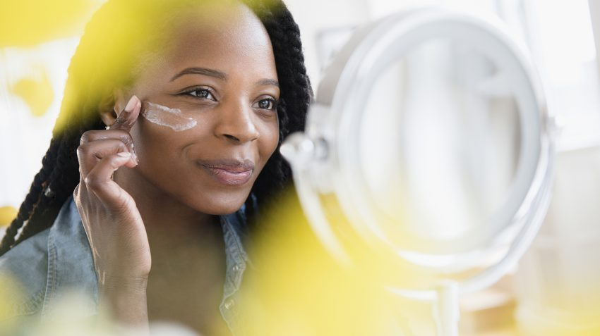 Woman applying skincare cream to cheek