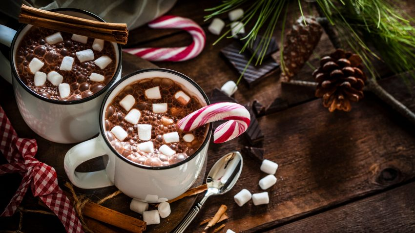 Two mugs of hot chocolate with marshmallows and candy canes