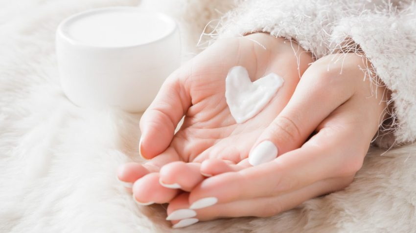 moisturizer in shape of a heart in woman's palms